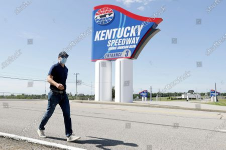 Driver Jimmie Johnson walks past a sign after the street was named for him outside Kentucky Speedway before a NASCAR Cup Series auto race, in Sparta, Ky