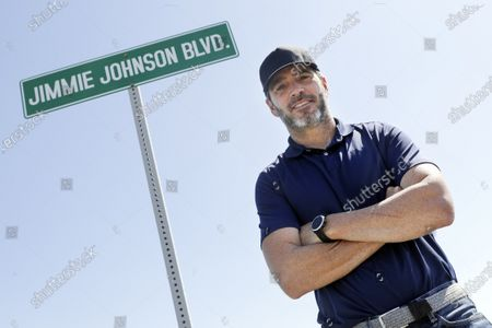Driver Jimmie Johnson poses in front of a street sign after the street was named for him outside Kentucky Speedway before a NASCAR Cup Series auto race, in Sparta, Ky