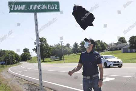 Driver Jimmie Johnson watches as the cover blows off a street sign as it is unveiled after the street was named for him outside Kentucky Speedway before a NASCAR Cup Series auto race, in Sparta, Ky