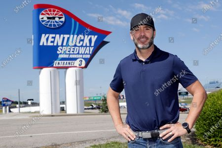 Driver Jimmie Johnson poses in front of a track entrance sign after the street was named for him outside Kentucky Speedway before a NASCAR Cup Series auto race, in Sparta, Ky