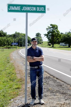 Driver Jimmie Johnson poses with a street sign after the street was named for him outside Kentucky Speedway before a NASCAR Cup Series auto race, in Sparta, Ky