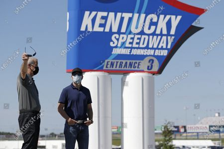 Driver Jimmie Johnson, right, talks with Kentucky Speedway general manager Mark Simendinger in front of a track entrance sign after the street was named for Johnson before a NASCAR Cup Series auto race, in Sparta, Ky