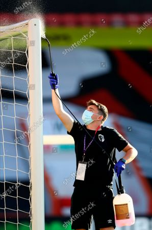 A staff member disinfects the goal post during during the English Premier League match between AFC Bournemouth and Leicester City in Bournemouth, Britain, 12 July 2020.