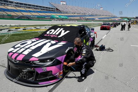 Crew member checks a tire on Jimmie Johnson's car before a NASCAR Cup Series auto race, in Sparta, Ky