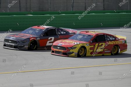 Brad Keselowski (2) and Ryan Blaney (12) work during a NASCAR Cup Series auto race, in Sparta, Ky