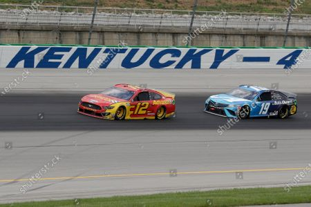 Ryan Blaney (12) and Martin Truex Jr. (19) run during a NASCAR Cup Series auto race, in Sparta, Ky