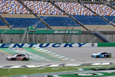 Cole Custer (41) crosses the finish line ahead of Martin Truex Jr. (19) after winning a NASCAR Cup Series auto race, in Sparta, Ky