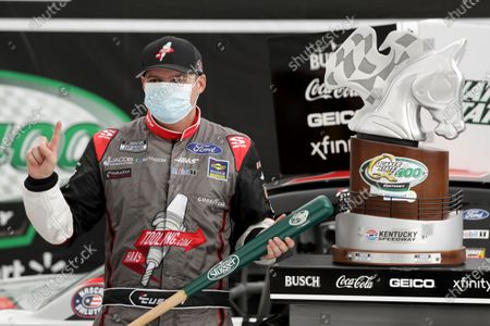 Cole Custer celebrates with the trophy after winning a NASCAR Cup Series auto race, in Sparta, Ky