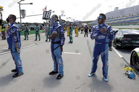 Bubba Wallace, right, stands for the National Anthem before the start of a NASCAR Cup Series auto race, in Sparta, Ky