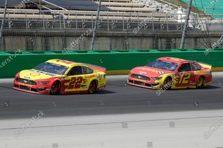 Joey Logano. Left, and Ryan Blaney (12) work during a NASCAR Cup Series auto race, in Sparta, Ky