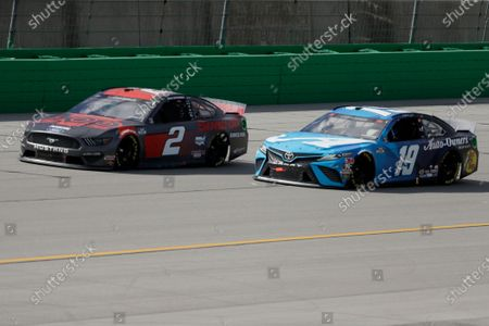 Brad Keselowski, left, and Martin Truex Jr. work during a NASCAR Cup Series auto race, in Sparta, Ky