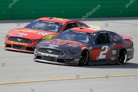 Ryan Blaney, left, and Brad Keselowski (2) run during a NASCAR Cup Series auto race, in Sparta, Ky