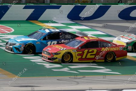 Martin Truex Jr. (19) and Ryan Blaney (12) run during a NASCAR Cup Series auto race, in Sparta, Ky