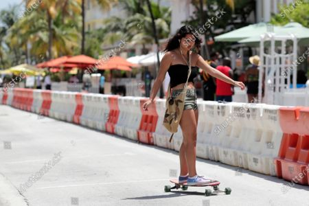 Girl skateboards down Ocean Drive during the coronavirus pandemic, in Miami Beach, Fla. Florida on Sunday reported the largest single-day increase in positive coronavirus cases in any one state since the beginning of the pandemic