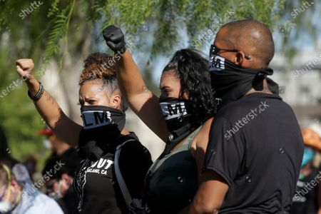 Stock Picture of Brittany Taylor, from left, raises her fist next to sister-in-law Jessica Ramirez-Taylor and her brother and Ramirez-Taylor's husband Chris Taylor as they take a knee for eight minutes 46 seconds in memory of George Floyd in Martinez, Calif., during a protest calling for an end to racial injustice and accountability for police