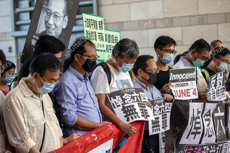 Stock Image of Pro-democracy activist and former lawmaker Lee Cheuk-yan (C) observes a minute of silence, for the late Chinese dissident and Noble Peace Price recipient Liu Xiaobo on the third anniversary of his death, outside the West Kowloon Magistrates' Court in Hong Kong, China, 13 July 2020. Lai is among 13 leading Hong Kong opposition figures to be summoned to court for illegal assembly charges related to taking part in a banned public meeting, the annual Tiananmen Massacre vigil, on 04 June 2020.