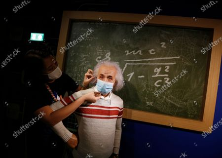 Stock Picture of A staff member puts a mask on a wax statue of theoretical physicist Albert Einstein at the Madame Tussauds Museum in Bangkok, Thailand, 13 July 2020. According to local media reports, Thailand is expected to produce a vaccine for COVID19 by the third quarter of 2021. The first phase of human trials will begin in October 2020 with over 10,000 participants between Thai nationals and foreigners, Thai Professor of Chula Vaccine Research Center, Kiat Ruxrungtham said.