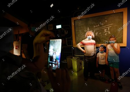 Stock Image of Visitors pose next to a wax statue of theoretical physicist Albert Einstein at the Madame Tussauds Museum in Bangkok, Thailand, 13 July 2020. According to local media reports, Thailand is expected to produce a vaccine for COVID19 by the third quarter of 2021. The first phase of human trials will begin in October 2020 with over 10,000 participants between Thai nationals and foreigners, Thai Professor of Chula Vaccine Research Center, Kiat Ruxrungtham said.