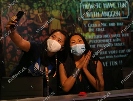 A woman poses for a photo next to a wax figure of Indonesian singer Anggun wearing a face mask at the Madame Tussauds Museum in Bangkok, Thailand, 13 July 2020. According to local media reports, Thailand is expected to produce a vaccine for COVID19 by the third quarter of 2021. The first phase of human trials will begin in October 2020 with over 10,000 participants between Thai nationals and foreigners, Thai Professor of Chula Vaccine Research Center, Kiat Ruxrungtham said.