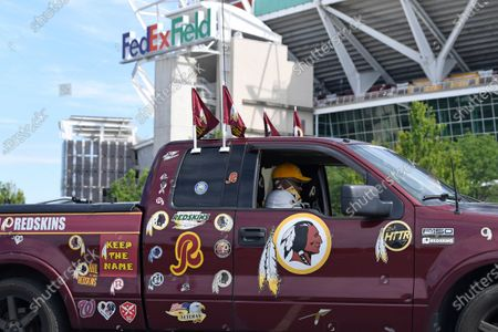 "Rodney Johnson of Chesapeake, Va., sits in his truck outside FedEx Field in Landover, Md., . The Washington NFL franchise announced Monday that it will drop the ""Redskins"" name and Indian head logo immediately, bowing to decades of criticism that they are offensive to Native Americans"