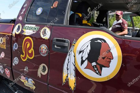 "Rodney Johnson of Chesapeake, Va., stands with his truck outside FedEx Field in Landover, Md., . The Washington NFL franchise announced Monday that it will drop the ""Redskins"" name and Indian head logo immediately, bowing to decades of criticism that they are offensive to Native Americans"