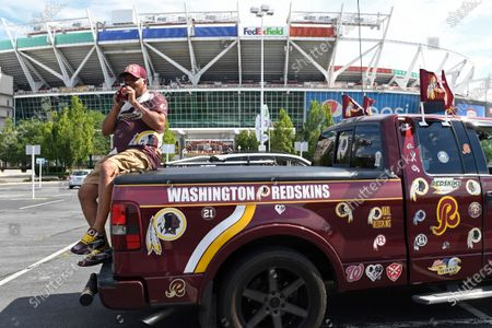 "Rodney Johnson of Chesapeake, Va., sits on the back of his truck outside FedEx Field in Landover, Md., . The Washington NFL franchise announced Monday that it will drop the ""Redskins"" name and Indian head logo immediately, bowing to decades of criticism that they are offensive to Native Americans"
