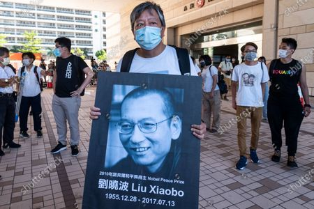 Hong Kong politician and social activist Lee Cheuk-yan holds an image of Chinese dissident and Nobel Peace Prize recipient Liu Xiaobo after attending a mention at the West Kowloon Magistrates Court. 13 activists who led the 2020´s Tiananmen Square crackdown candlelight vigil on June 4th appeared in court and they were charged for holding an unauthorized gathering.