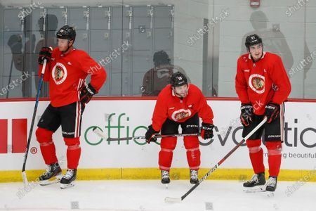 Chicago Blackhawks' Jonathan Toews, left, Alex DeBrincat, center, and Kirby Dach, right, taking a break from skating during NHL hockey practice at Fifth Third Arena, in Chicago
