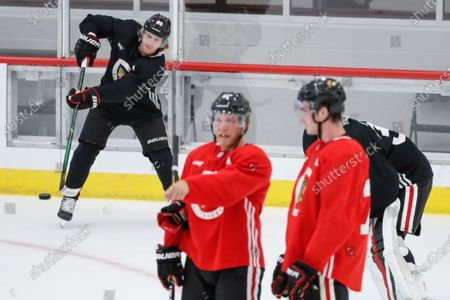 Chicago Blackhawks right wing Patrick Kane, left, hits the puck during NHL hockey practice at Fifth Third Arena, in Chicago