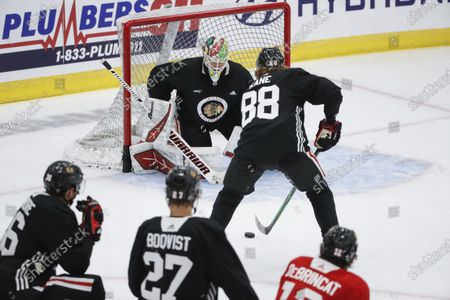 Chicago Blackhawks goaltender Collin Delia, center, defends against right wing Patrick Kane during NHL hockey practice at Fifth Third Arena, in Chicago