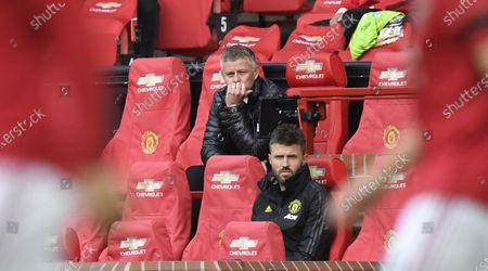 Manchester United's manager Ole Gunnar Solskjaer (L) and assistant Michael Carrick (R) sit on the bench during the English Premier League match between Manchester United and Southampton FC in Manchester, Britain, 13 July 2020.