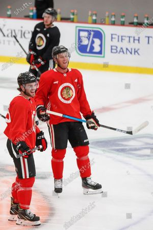 Stock Photo of Chicago Blackhawks left wing Alex DeBrincat, left, jokes with center Jonathan Toews, right, during NHL hockey practice at Fifth Third Arena, in Chicago