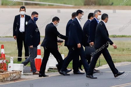 Horacio Cartes (C- covered) and Mauricio Macri (2-R), flanked by private guards of former Paraguayan President arrive to a private hangar in the city of Luque, Paraguay, 13 July 2020. Former President of Argentina Mauricio Macri, left Asuncion on Monday after meeting former President Horacio Cartes (2013-2018) and President Mario Abdo Benitez, on a visit of less than 24 hours as the country's borders still closed due to the health quarantine.