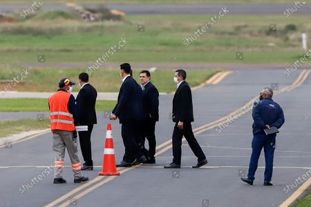 Horacio Cartes (C- without masks) flanked by private guards at a private hangar in the city of Luque, Paraguay, 13 July 2020. Former President of Argentina Mauricio Macri, left Asuncion on Monday after meeting former President Horacio Cartes (2013-2018) and President Mario Abdo Benitez, on a visit of less than 24 hours as the country's borders still closed due to the health quarantine.