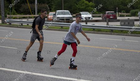Andrew Walker (R) and Jacob Adkins, UMass Boston roommates and UMass Boston Hockey teammates, rollerblade on route 20 in Auburn, Massachusetts, USA 13 July 2020, as part of their Massachusetts to Michigan fundraiser for the American Cancer Society's life-saving mission. The two 21-year olds have seen cancer up close in their families and hope to complete the approximately 875 miles (1400 km) from Boston to Mason, Michigan, in seven to ten days.