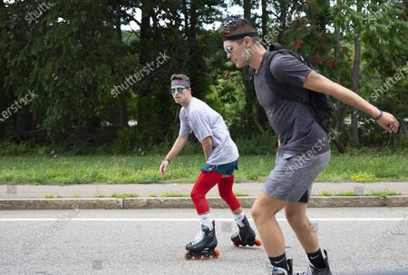 Stock Image of Andrew Walker (L) and Jacob Adkins, UMass Boston roommates and UMass Boston Hockey teammates, rollerblade on route 20 in Auburn, Massachusetts, USA 13 July 2020, as part of their Massachusetts to Michigan fundraiser for the American Cancer Society's life-saving mission. The two 21-year olds have seen cancer up close in their families and hope to complete the approximately 875 miles (1400 km) from Boston to Mason, Michigan, in seven to ten days.