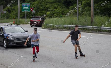 Andrew Walker (L) and Jacob Adkins, UMass Boston roommates and UMass Boston Hockey teammates, rollerblade on route 20 in Auburn, Massachusetts, USA 13 July 2020, as part of their Massachusetts to Michigan fundraiser for the American Cancer Society's life-saving mission. The two 21-year olds have seen cancer up close in their families and hope to complete the approximately 875 miles (1400 km) from Boston to Mason, Michigan, in seven to ten days.