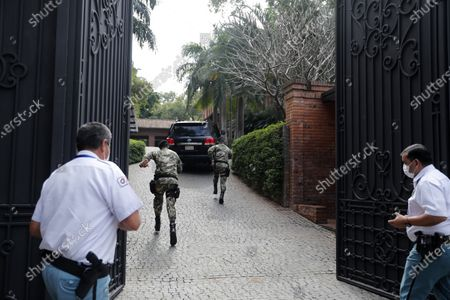 Military and security personnel run behind the car carrying Argentina's former President Mauricio Macri into the house of Paraguay's former President Horacio Cartes in Asuncion, Paraguay, . Macri is in a 24 hours visit to Paraguay