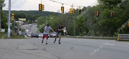 Andrew Walker (L) and Jacob Adkins, UMass Boston roommates and UMass Boston Hockey teammates, rollerblade on route 20 in Oxford, Massachusetts, USA 13 July 2020, as part of their Massachusetts to Michigan fundraiser for the American Cancer Society's life-saving mission. The two 21-year olds have seen cancer up close in their families and hope to complete the approximately 875 miles (1400 km) from Boston to Mason, Michigan, in seven to ten days.