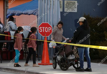"The Gomez family twin girls, with their mother from Oaxaca, Mexico, middle, pick up ""Grab & Go"" meals provided by the Los Angeles Unified District at the Robert F. Kennedy Community School station in Los Angeles. Amid spiking coronavirus cases, Los Angeles Unified School District campuses will remain closed when classes resume next month, Superintendent Austin Beutner said, defying President Donald Trump's demand that students return to in-person instruction"