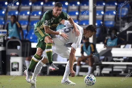 Portland Timbers midfielder Marvin Loria, left, is separated from the ball by LA Galaxy defender Daniel Steres (5) during the first half of an MLS soccer match, in Kissimmee, Fla