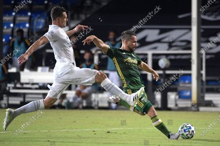 Portland Timbers midfielder Sebastian Blanco, right, attempts a shot in front of LA Galaxy defender Daniel Steres during the first half of an MLS soccer match, in Kissimmee, Fla