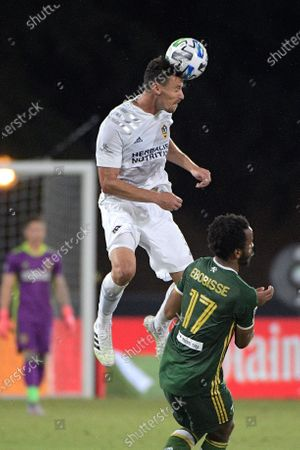Galaxy defender Daniel Steres wins a header over Portland Timbers forward Jeremy Ebobisse (17) during the second half of an MLS soccer match, in Kissimmee, Fla