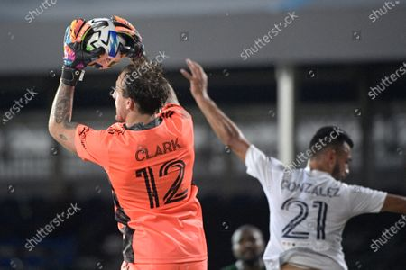 Portland Timbers goalkeeper Steve Clark (12) makes a save in front of LA Galaxy defender Giancarlo Gonzalez (21) during the second half of an MLS soccer match, in Kissimmee, Fla