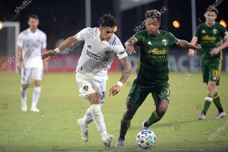 Galaxy forward Cristian Pavon (10) controls the ball in front of Portland Timbers forward Andy Polo (7) during the second half of an MLS soccer match, in Kissimmee, Fla