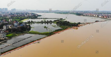 Aerial photo taken on July 13, 2020 shows water of Changjiang River about to flow over an embankment near Poyang County, east China's Jiangxi Province.   With the rising water of Changjiang River about to flow over the embankment near Poyang County, armed police troops came to join the flood control operations that built a 1,500-meter-long and 1.5-meter-high barrier on the embankment.  Liu Yifei, Ma Paishan, Yang Zeyu, Yuan Long, and Zhu Renpeng, who were all born after 2000, have for the first time joined such a flood control battle since they joined the troop. Almost every day over the past week, they did their utmost to carry and pile sandbags along the embankment while enduring sweltering weather.