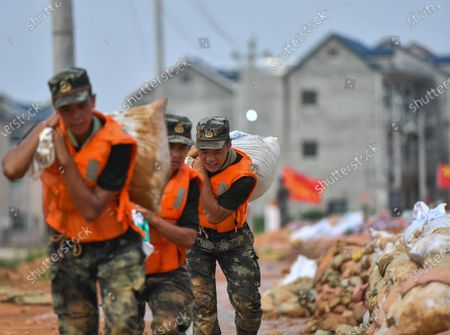 Armed police officer Liu Yifei (1st R) carries a sandbag on the embankment in Poyang County, east China's Jiangxi Province, July 13, 2020.   With the rising water of Changjiang River about to flow over the embankment near Poyang County, armed police troops came to join the flood control operations that built a 1,500-meter-long and 1.5-meter-high barrier on the embankment.  Liu Yifei, Ma Paishan, Yang Zeyu, Yuan Long, and Zhu Renpeng, who were all born after 2000, have for the first time joined such a flood control battle since they joined the troop. Almost every day over the past week, they did their utmost to carry and pile sandbags along the embankment while enduring sweltering weather.