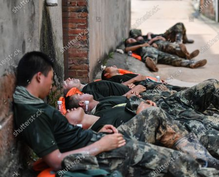 Armed police officers take a nap outside houses of local residents in Poyang County, east China's Jiangxi Province, July 13, 2020.   With the rising water of Changjiang River about to flow over the embankment near Poyang County, armed police troops came to join the flood control operations that built a 1,500-meter-long and 1.5-meter-high barrier on the embankment.  Liu Yifei, Ma Paishan, Yang Zeyu, Yuan Long, and Zhu Renpeng, who were all born after 2000, have for the first time joined such a flood control battle since they joined the troop. Almost every day over the past week, they did their utmost to carry and pile sandbags along the embankment while enduring sweltering weather.