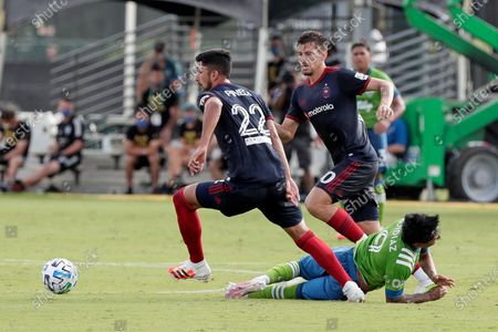 Chicago Fire defender Mauricio Pineda (22) and midfielder Alvaro Medran, center, move the ball after getting past fallen Seattle Sounders forward Raul Ruidiaz, lower right, during the first half of an MLS soccer match, in Kissimmee, Fla