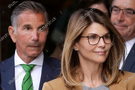 Actress Lori Loughlin, front, and her husband, clothing designer Mossimo Giannulli, left, depart federal court in Boston after a hearing in a nationwide college admissions bribery scandal. In a court filing, lawyers for the couple, who admitted to paying $500,000 to get their daughters into the University of Southern California as fake crew recruits, asked a judge to lower their bail from $1 million to $100,000, saying they will not flee ahead of their August sentencing in the college admissions bribery case